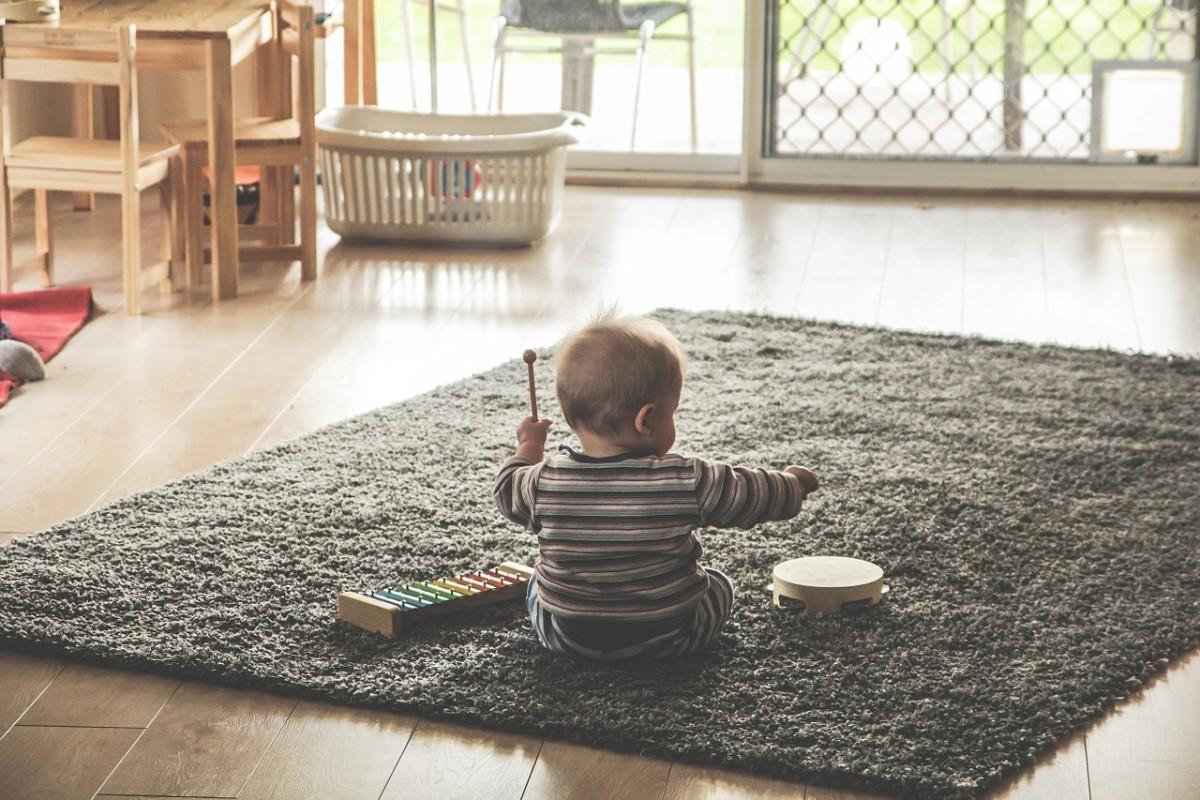 Cuarto lleno de luz natural con un bebé sentado escuchando música