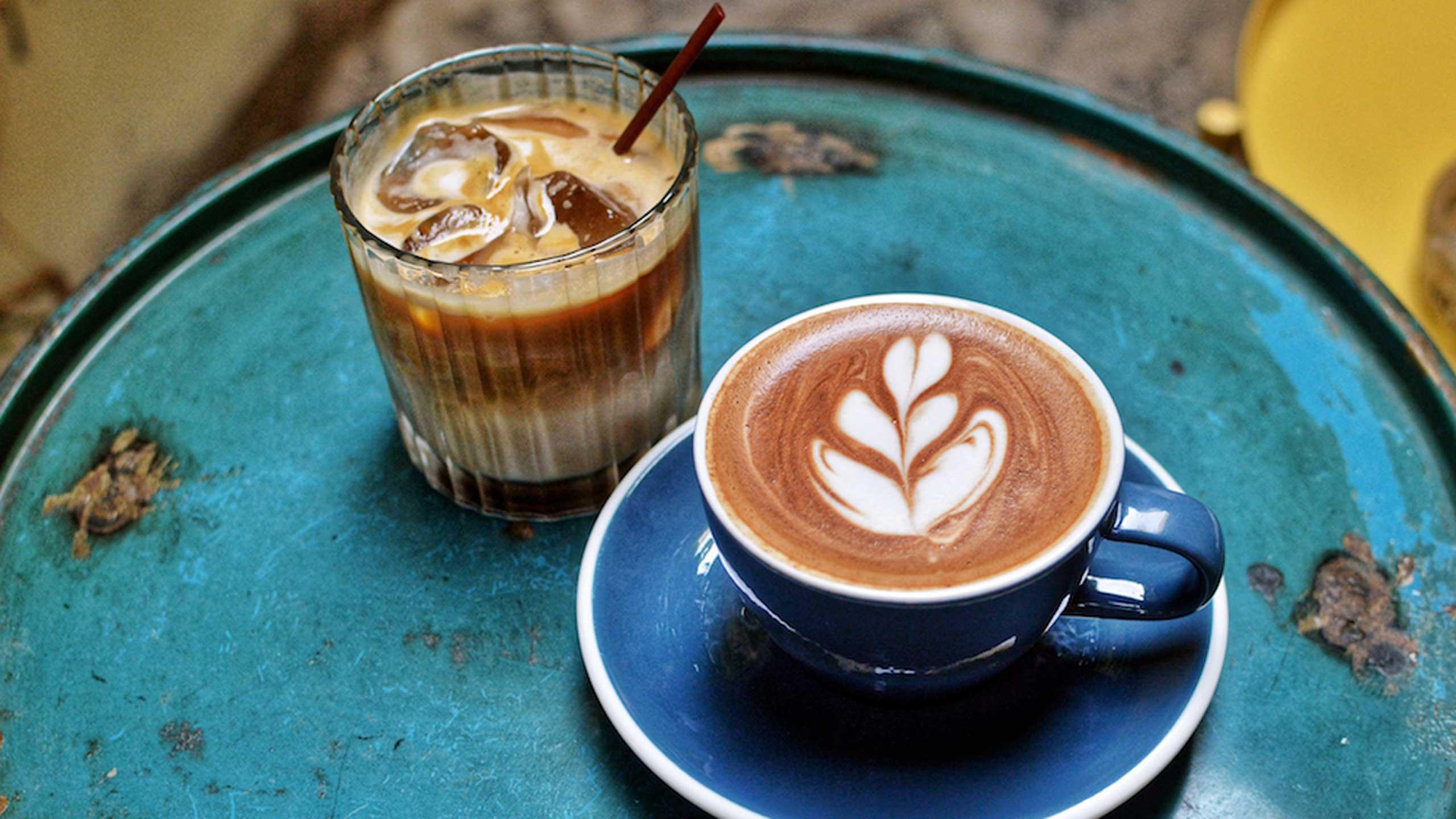 taza de café con leche a un costado de un vaso con carajillo